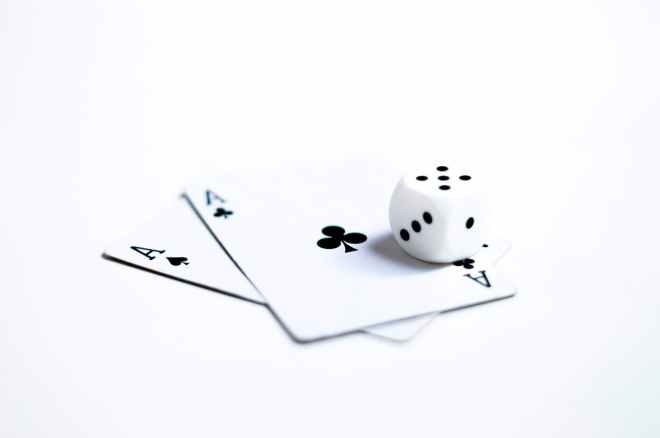 white and black dice on two ace of clubs and spades cards